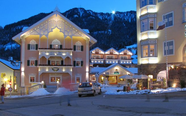 Hotele w centrum Ortisei. Na grani widać reflektory zapalone na górnej stacji gondoli na Alpe di Siusi.