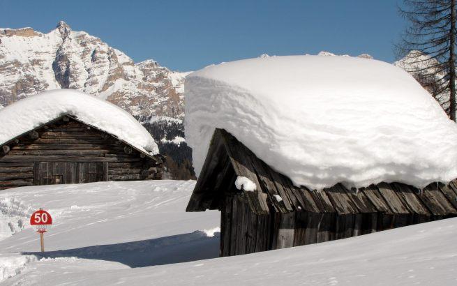 Szałasy w Colfosco po dużych opadach śniegu.